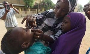 Health workers immunise a child in Nigeria