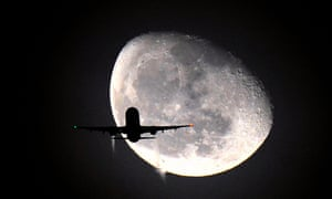 A plane is silhouetted against the waning moon over London, UK.
