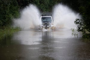 A Four wheel drive navigates through floodwater near Muirs Creek.