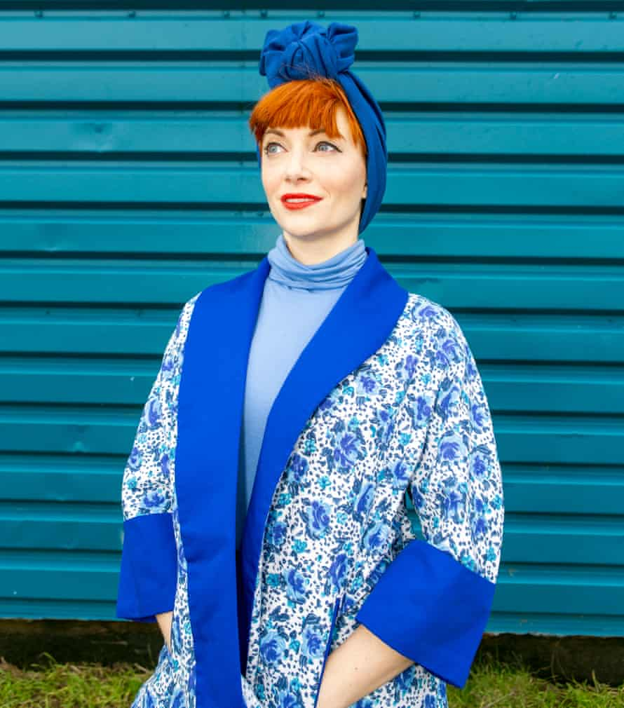Amber Butchart wearing a blue patterned, kimono-style jacket over a blue polo neck, with a royal blue turban