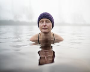 woman in water up to her shoulders, eyes closed