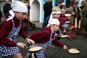 Schoolchildren take part in a pancake race on 9 February in Olney, Buckinghamshire