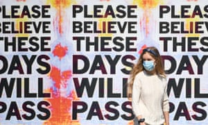 Masked woman in front of 'These days will pass' posters
