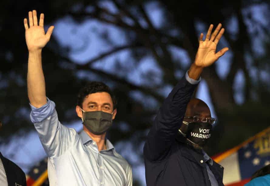 Democratic Senate candidates Jon Ossoff and the Rev Raphael Warnock wave to supporters during a drive-in campaign event in Columbus on 29 October.