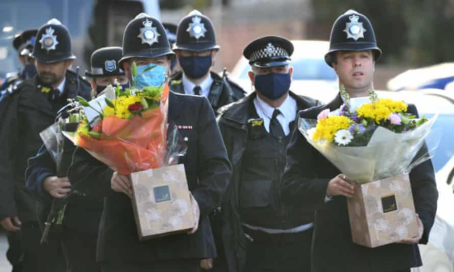 Police officers with flowers arrive at Croydon Custody Centre in south London where a police officer was shot.