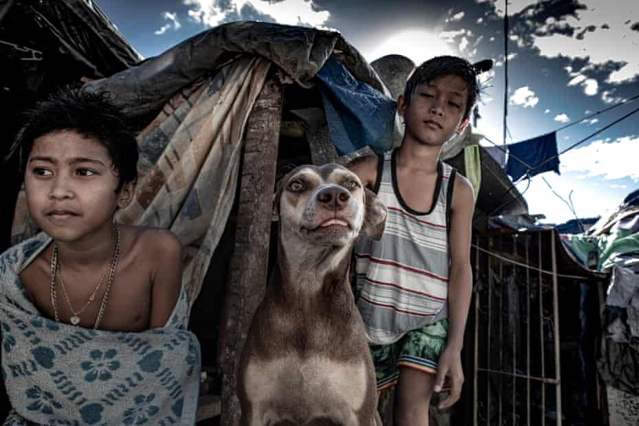 Two young inhabitants of Pasay cemetery with their dog.