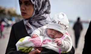 A Syrian refugee holds a baby
