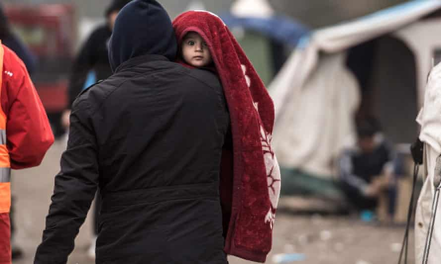 refugee with a child in the camp of Grande-Synthe, near Dunkirk