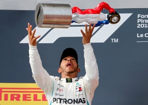 Hamilton celebrates with the trophy.