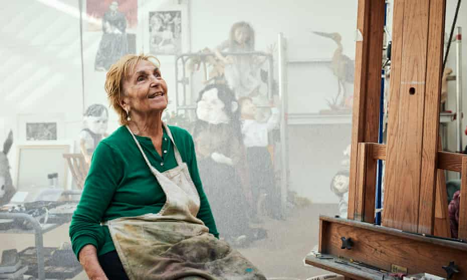 Paula Rego in her studio wearing a paint-spattered apron and smiling