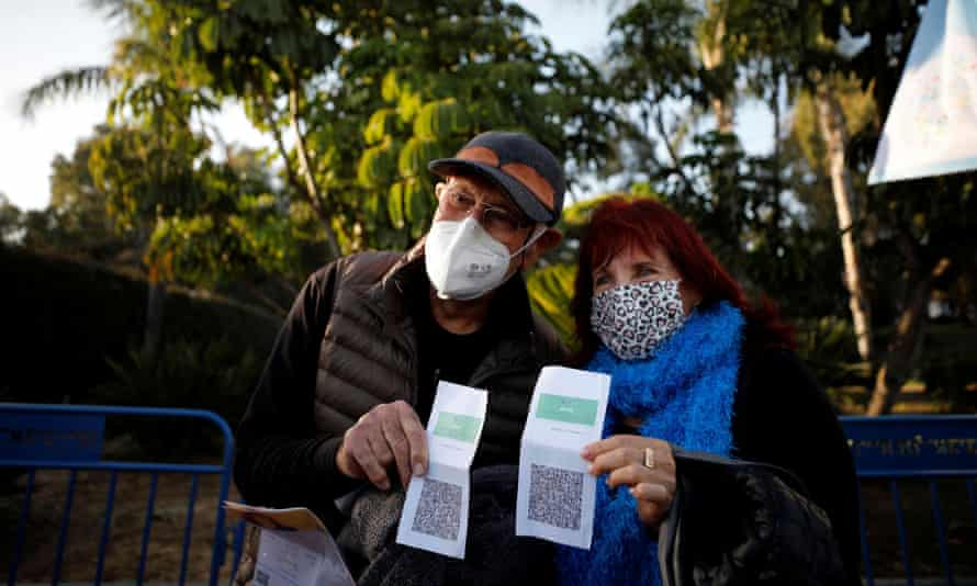 Vaccinated seniors pose with their green passes at a concert in Yarkon park, in Tel Aviv.