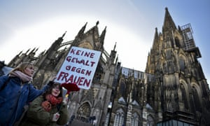 Protesters gather outside Cologne Cathedral on Saturday with a sign reading 'No violence against women'.
