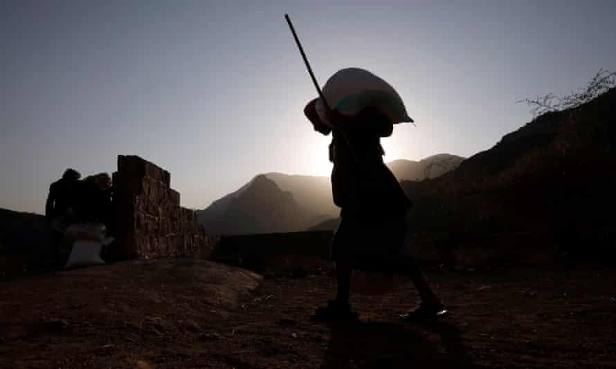 A man carries food rations in Yemen
