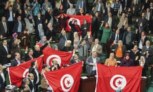 Members of the Tunisian national constituent assembly celebrate the adoption of the new constitution in 2014.