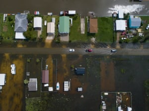 Cars drive on a flooded street in Sargent, Texas.