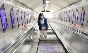 A woman wearing a mask on the London Underground during the coronavirus outbreak. Experts say social distancing will impact the rate of fatalities.