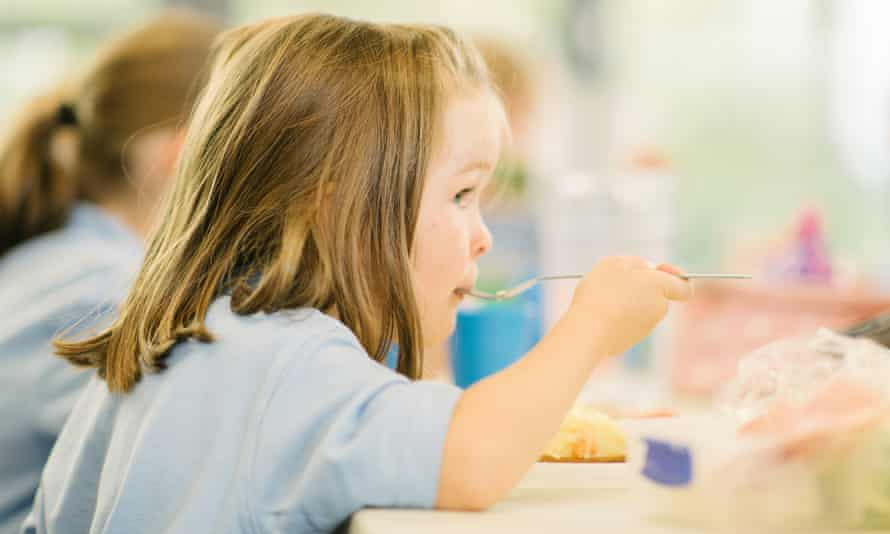 Young girl eating a school dinner