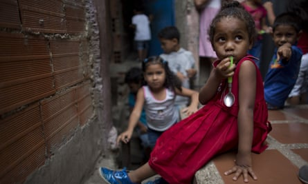 A young girl sits on a wall in a slum neighbourhood with a spoon in her mouth