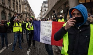A man holds a french flag during a gilets jaunes protest in Paris on Saturday