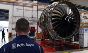 A Rolls-Royce worker in front of an engine