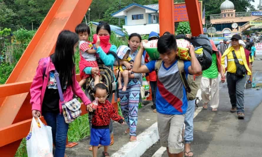 Filipino villagers fleeing with their belongings as fighting between Maute militants and government forces continued in Marawi.
