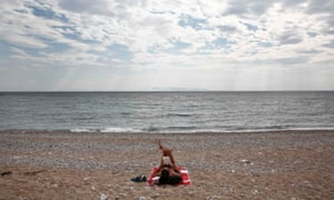 Getting away from it all … a man reads a book at a beach in Glyfada, a suburb of Athens.