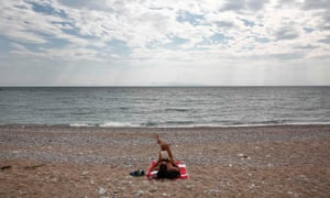 A man reads a book on a beach in Glyfada, south-east of Athens, Greece.