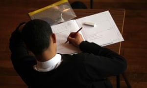 Pupil taking exam in school hall