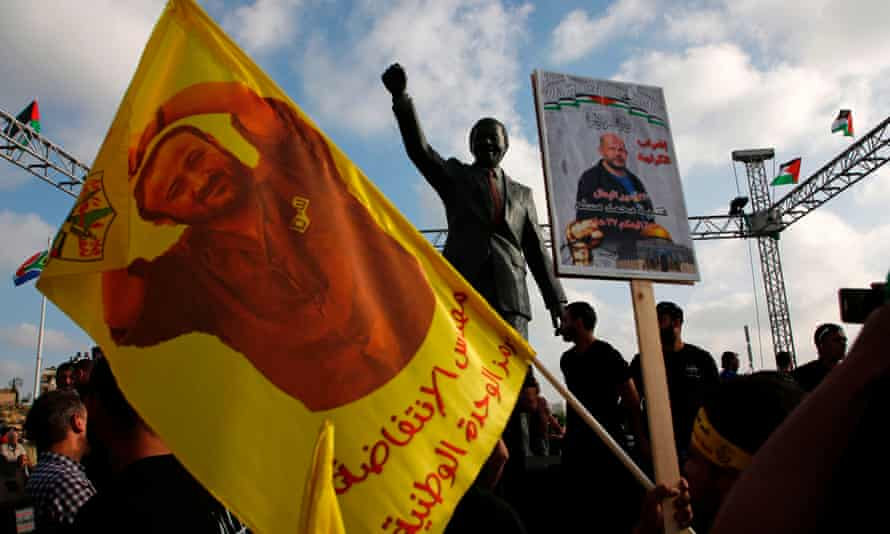 Protesters wave flags and portraits of Palestinian leader and prisoner Marwan Barghouti in the West Bank city of Ramallah.