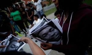 Demonstrators distribute photos of Paul O'Neal before protesting his fatal shooting by a Chicago police officer.