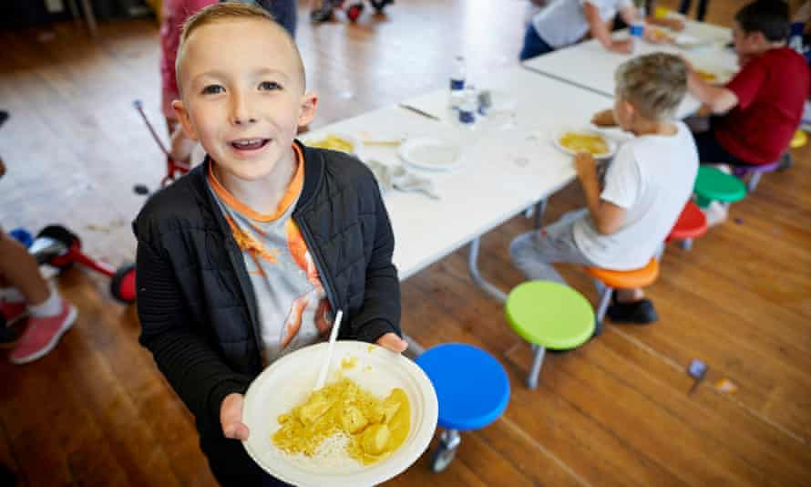 Eight-year-old Michael Medenica eating a Can Cook Kitchen curry at Quayplay summer scheme in Flintshire, north Wales.