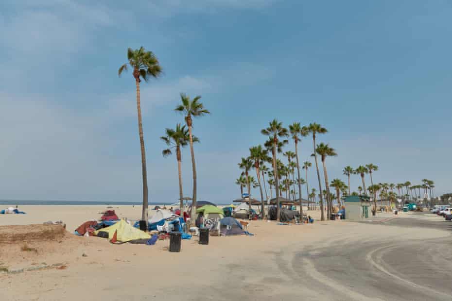 An encampment at Venice Beach next to the boardwalk and bike path.