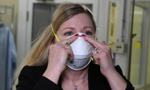 Nicole McCullough, a global health and safety expert at 3M, demonstrates the correct way to put on a N95 respiratory mask at a laboratory of 3M in Maplewood, Minnesota.