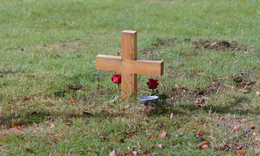 A burial cross in a garden
