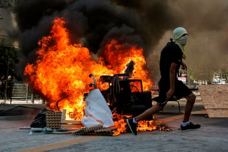 A demonstrator runs near a bonfire during a protest against the government's economic policies in Santiago on Wednesday.