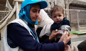 A Unicef employee measures the arm of a malnourished child in the besieged Syrian town of Madaya.