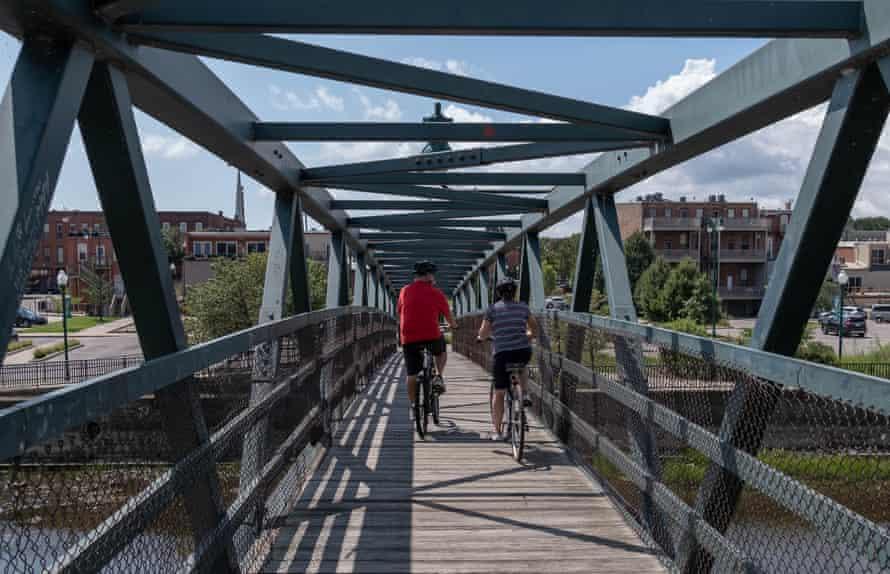 A couple rides their bikes across a bridge in Monroe this August.