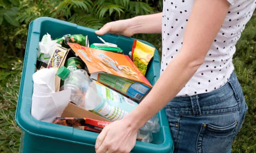 a woman takes her recycling box for roadside collection