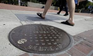 Pedestrians walk past a maintenance hole in Berkeley.
