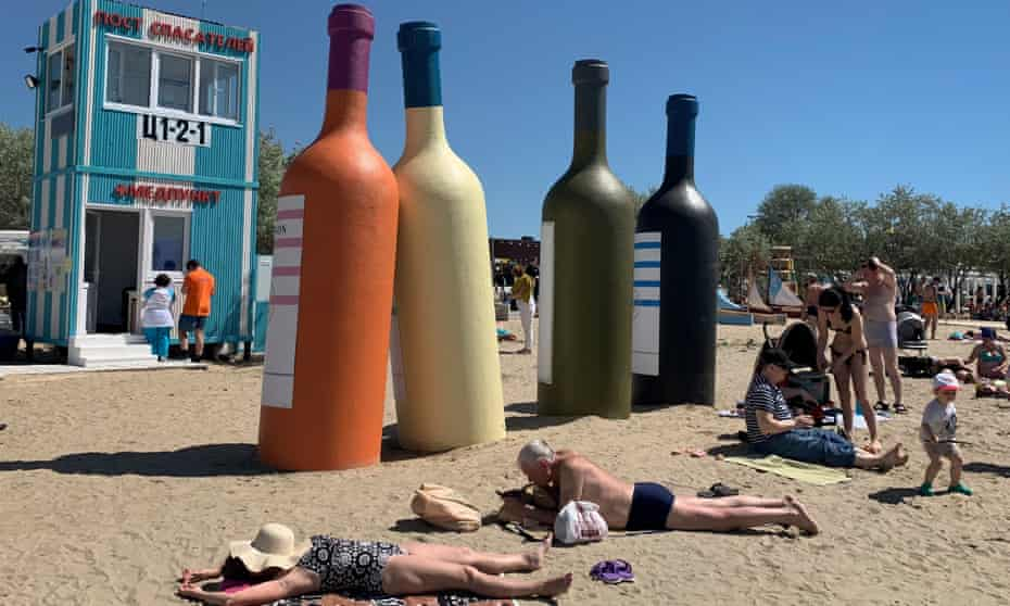 Tourists sunbathe next to imitation wine bottles during a wine festival in Anapa, Russia.