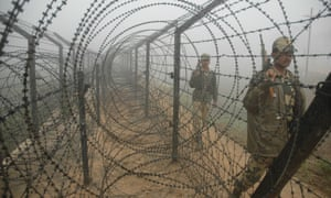 Indian soldiers patrol a section of barbed-wire fence along the border with Bangladesh