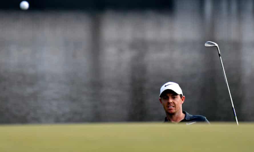 Rory McIlroy chips to the green on the 14th green after finding water off the tee.