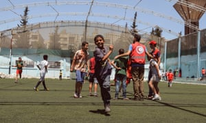 A refugee child on a football pitch runs towards the camera