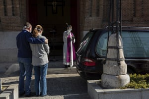 A priest wearing a face mask performs funeral rites at a Madrid cemetery in Madrid