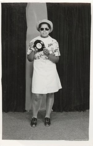A woman holds a Bobby Womack record while posing for a photo.
