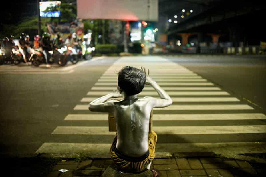A child wearing silver paint on their body, also known as a 'silverman', begging for money in Jakarta.