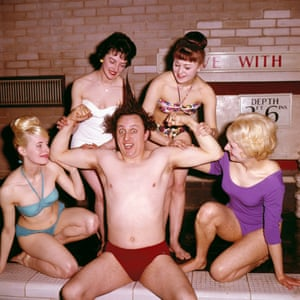 Dodd pictured wearing swimming trunks posing with four women in swimwear beside an indoor swimming pool in 1963.