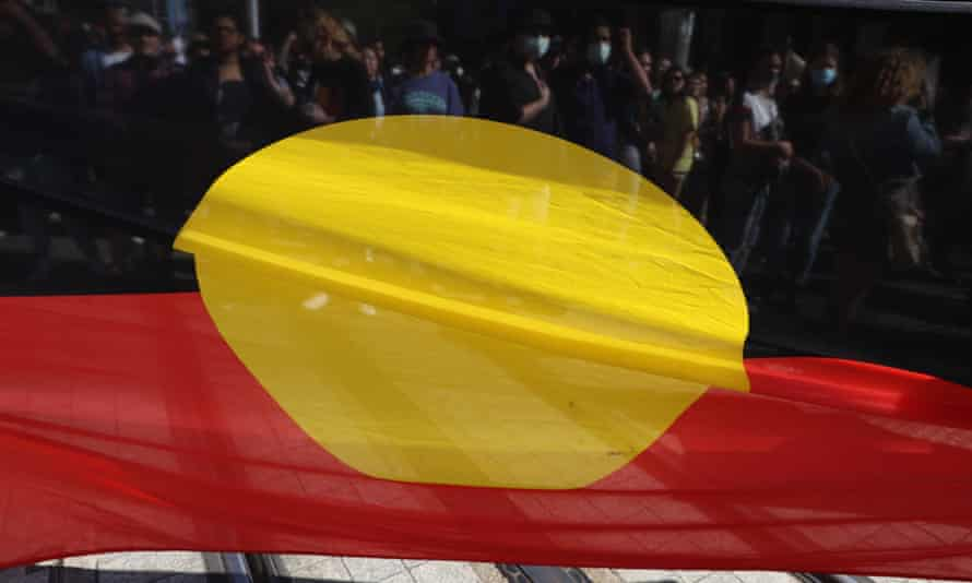 Protestors march with an Aboriginal flag during a rally on 10 April 2021 in Sydney, Australia.