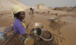 A woman sifts through mud as she looks for gold in Namisgma, the largest gold washing site in the country.