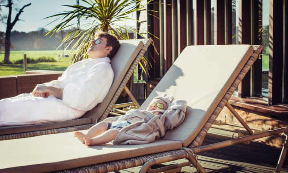 Seamus O'Reilly lying on one sun lounger and his baby son on another, both with pieces of cucumber over their eyes